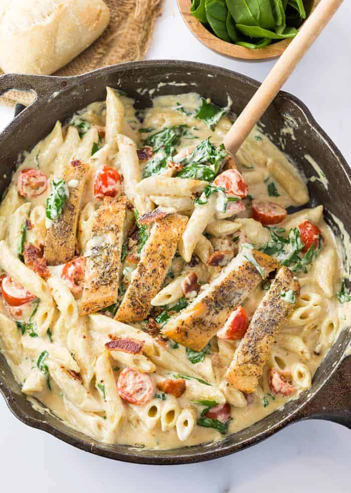 Creamy pasta with spinach and tomatoes topped with chicken in a cast iron pan with a wooden spoon.
