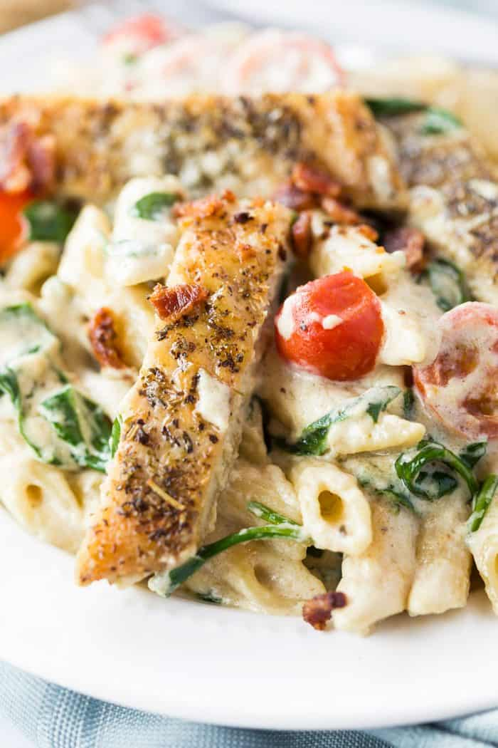 Close up image of seasoned and seared chicken next to a cherry tomato over pasta.