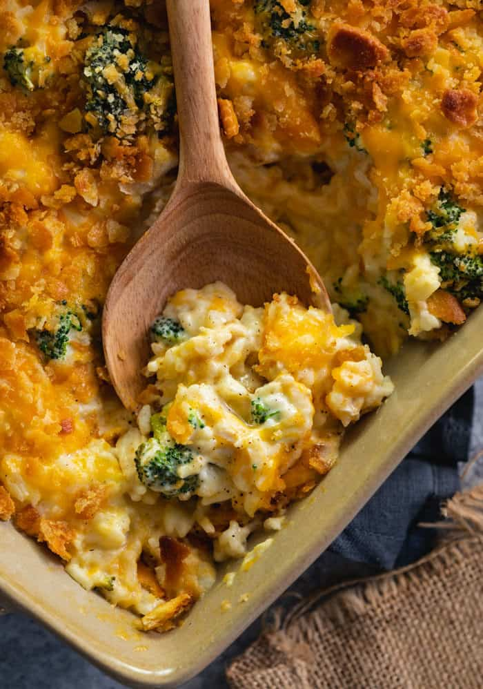 Casserole Dish filled with broccoli cheddar chicken and rice casserole with a wooden spoon scooping some out.