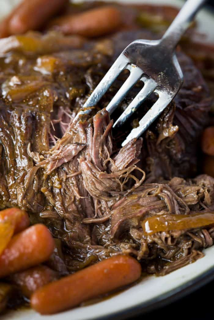 Close up view of tender pot roast with a fork sticking into it on a white plate with carrots.