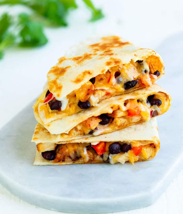 Crispy chicken quesadillas filled with black beans and melted cheese on a white surface.