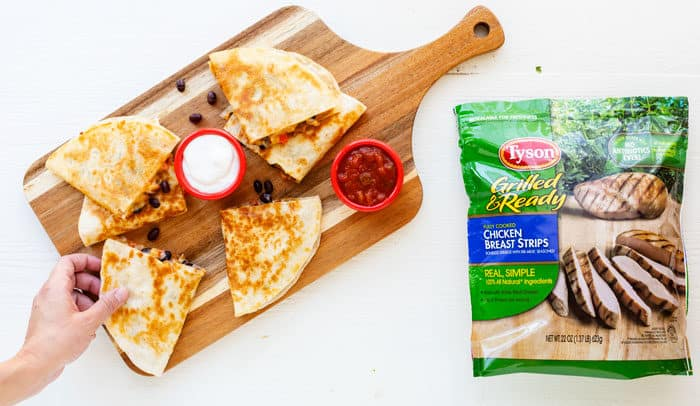 Wooden cutting board with chicken quesadillas on it next to a bag of Tyson grilled and ready chicken strips.