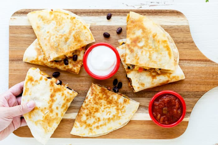 Wooden cutting board with crispy chicken quesadillas with sour cream and salsa. A hand is reaching for a quesadilla.