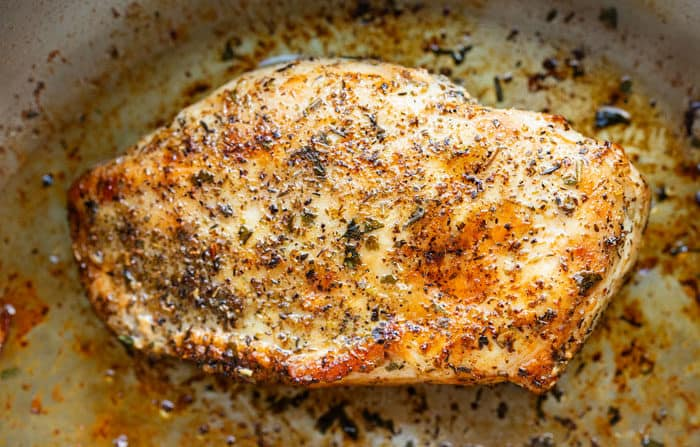 Seared and seasoned chicken in a frying pan.