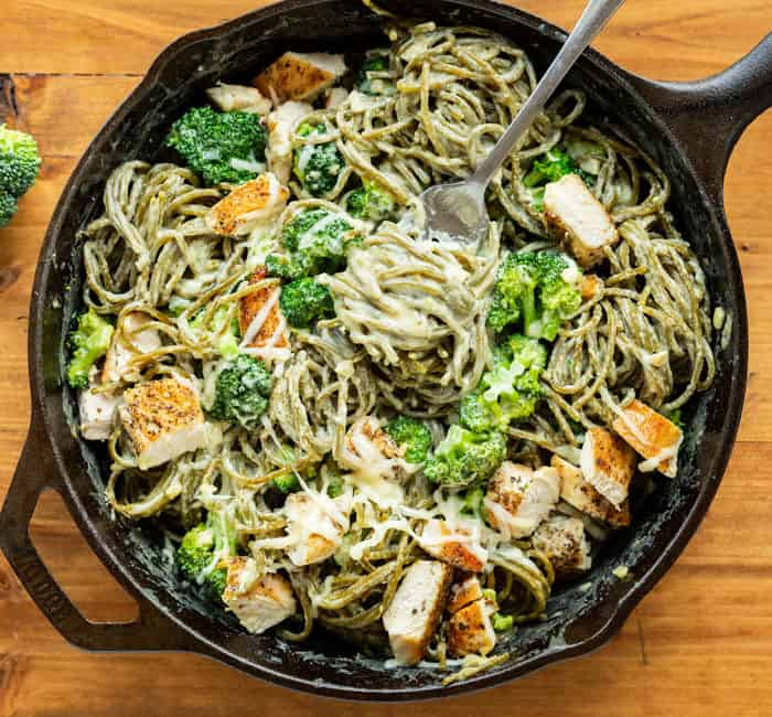 A cast iron skillet filled with Broccoli Pasta with Chicken in a creamy sauce and a fork with pasta.